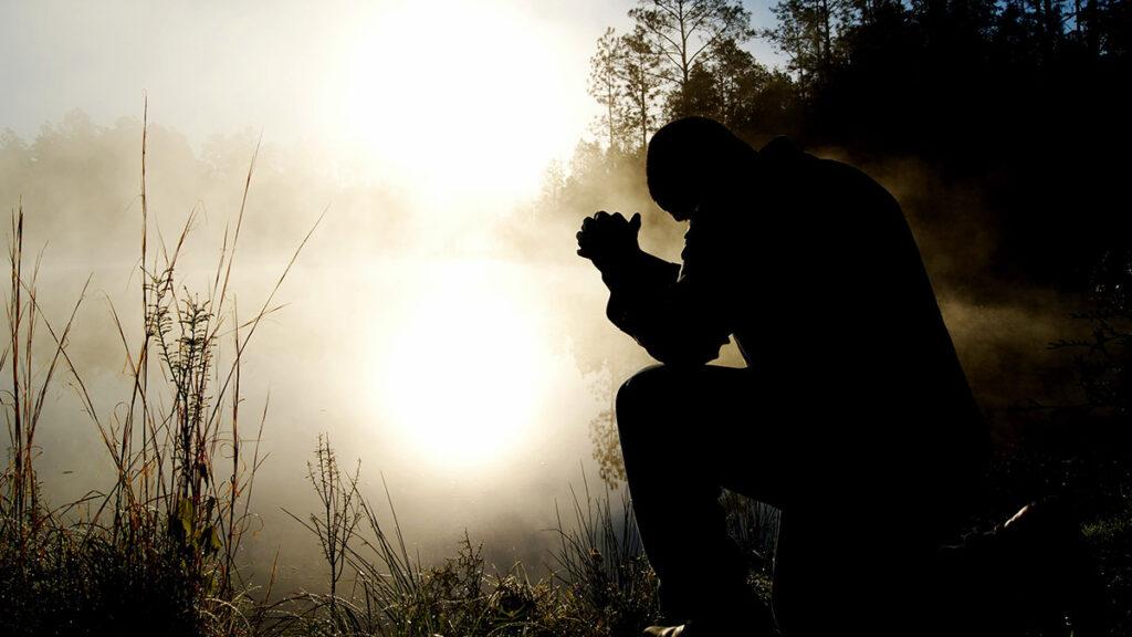 Человек молится на коленях Богу об избавлении зависимости: алкоголизма и наркомании